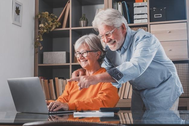 Gelukkig bejaard 60-er paar zitten thuis op de bank en betalen de huishoudelijke uitgaven online op de computer