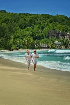 Gelukkig bejaard paar dat op een strand loopt
