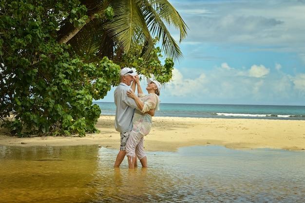 Gelukkig bejaarde echtpaar dansen op tropisch strand