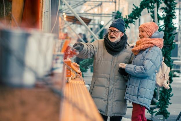 Gelukkig bejaarde echtpaar een bezoek aan de kerstmarkt en glimlachen. man wijst naar het straatvoedsel