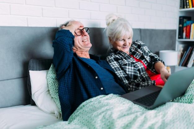Gelukkig bejaarde echtpaar in bed met laptop