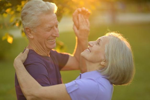 Gelukkig bejaarde echtpaar in de natuur op zonsondergang achtergrond