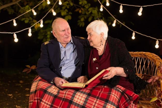 Gelukkig bejaarde echtpaar in het park, oma en opa. kijk naar het fotoalbum.