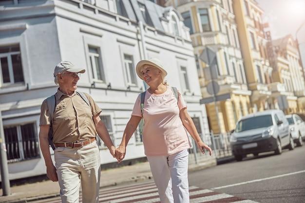 Gelukkig bejaarde echtpaar loopt hand in hand over het zebrapad