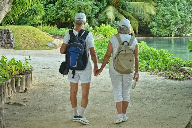 Gelukkig bejaarde echtpaar met rugzakken in tropische tuin buiten
