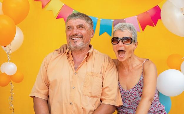 Gelukkig bejaarde echtpaar op gele achtergrond met ballonnen