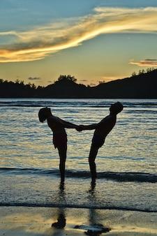 Gelukkig bejaarde echtpaar rust op tropisch strand bij zonsondergang
