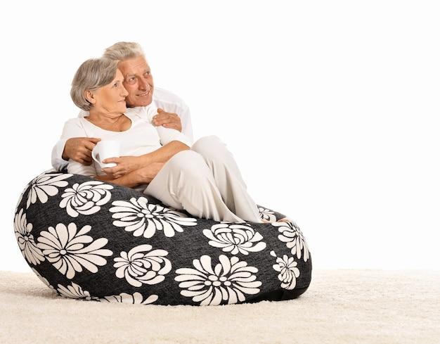 Gelukkig bejaarde echtpaar rust thuis zittend op kussen