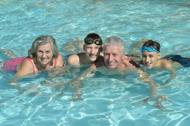 Gelukkig bejaarde echtpaar rusten bij het zwembad samen met kleinzonen