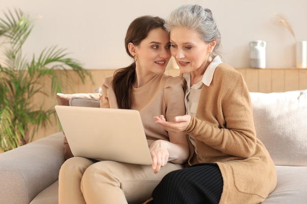 Gelukkig bejaarde middelste moeder zittend op de bank met haar dochter, laptop kijken. jonge vrouw toont video, foto's aan mama, vertrouwde relaties. familieconcept.