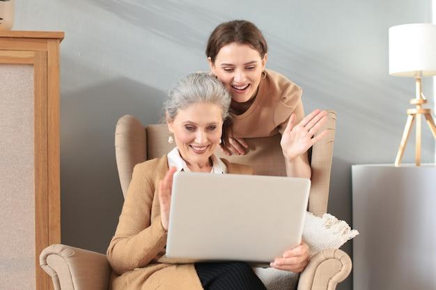 Gelukkig bejaarde middelste moeder zittend op een stoel met haar dochter, laptop kijken. jonge vrouw toont video, foto's aan mama, vertrouwde relaties. familieconcept.
