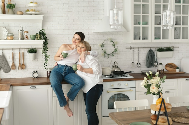 Gelukkig bejaarde moeder en dochter in de keuken, ze drinken thee en genieten van een gesprek. oude moeder met een volwassen dochter thuis