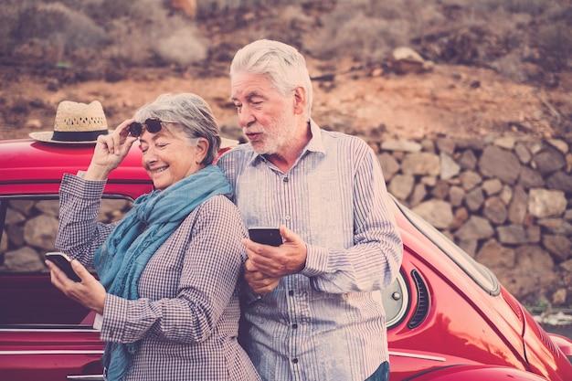 Gelukkig bejaarde senior paar gebruiken mobiele telefoons buiten in de buurt van een rode mooie retro auto. vrijetijdsbesteding en voor altijd samen reizen concept. modern gebruik van technologie van oude volwassenen die van het leven genoten