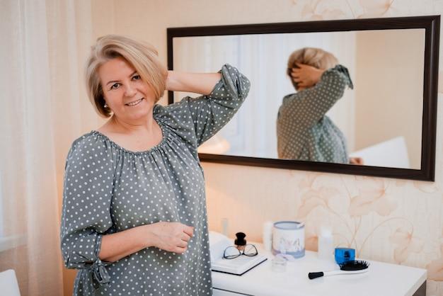 Gelukkig bejaarde vrouw van middelbare leeftijd strijkt haar glad en past haar haar aan voor de spiegel van de kaptafel