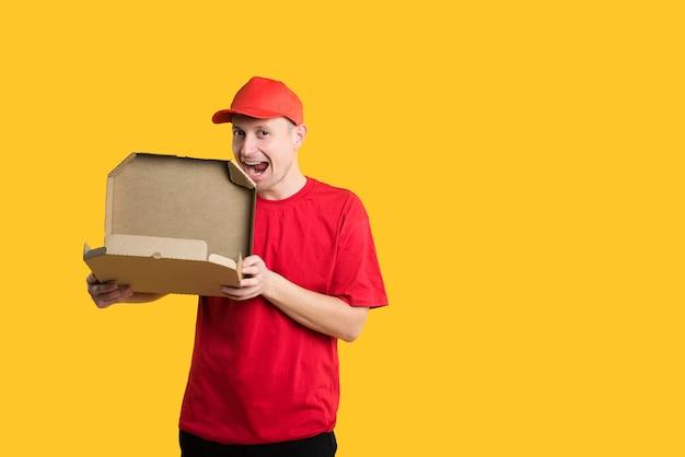 Gelukkig bezorger in rood uniform en doos op geel