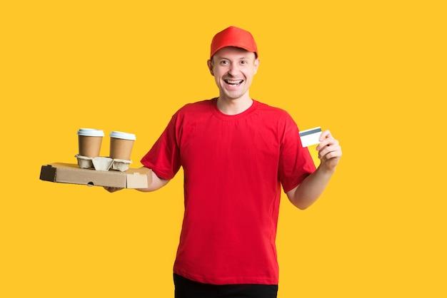 Gelukkig bezorger in rood uniform met doos, drankjes of koffie en creditcard op geel