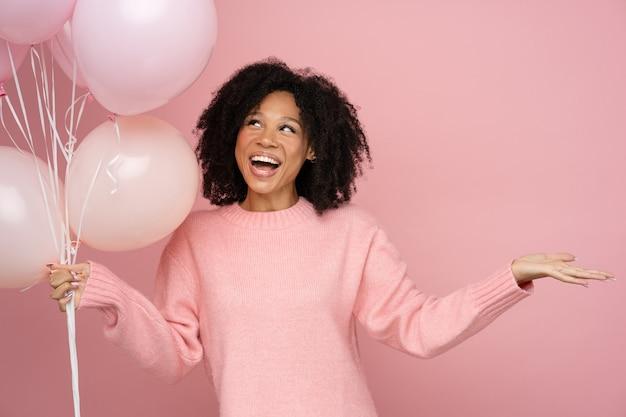 Gelukkig biracial vrouw met krullend haar met veel ballonnen