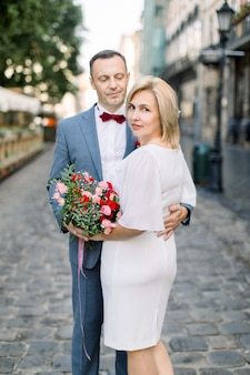 Gelukkig blank stel van middelbare leeftijd, poserend met een bloemboeket buiten in een prachtige oude stadsstraat
