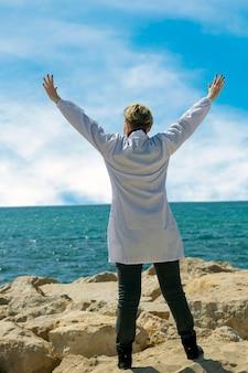 Gelukkig blanke amerikaanse medische vrouw in lab coat genieten van vrijheid met open handen op zee. zelfverzekerde vrouwelijke arts die zich voordeed op het strand. portret van een dokter die naar de zee loopt en zijn handen opsteekt Premium Foto