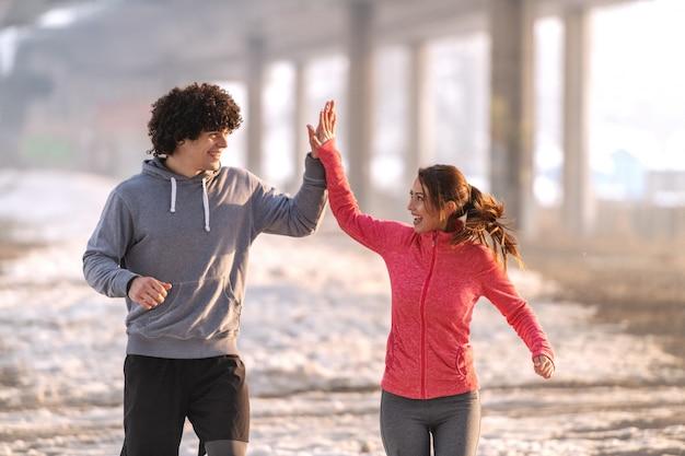 Gelukkig blanke lopers geven high five tijdens het hardlopen op het koude weer. overal sneeuw, wintertijd.