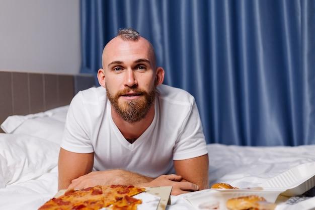 Gelukkig blanke man met fastfood thuis in de slaapkamer op bed man bestelde eten online om mee te nemen en eet pizza en hamburgers in een comfortabele kamer