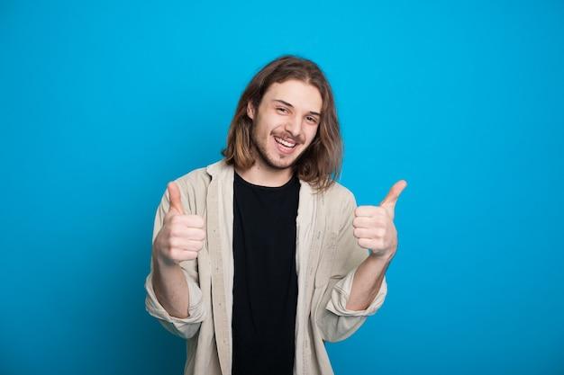 Gelukkig blanke man met lang haar en baard gebaren het soortgelijke teken op een blauwe muur