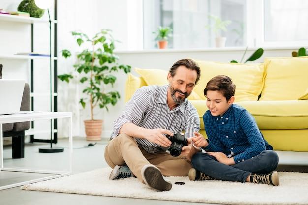 Gelukkig blanke man om thuis te zitten op het zachte tapijt met een camera in zijn handen en foto's te tonen aan zijn nieuwsgierige glimlachende zoon