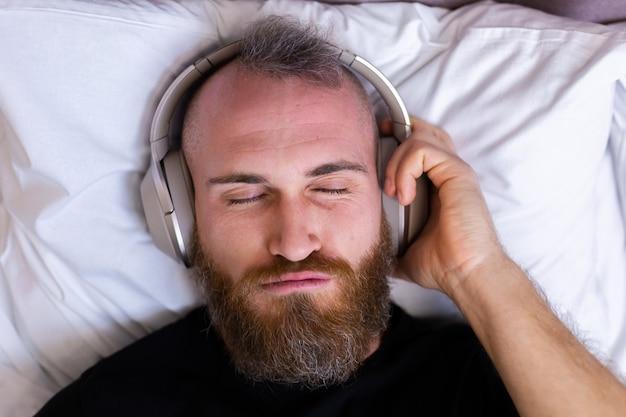 Gelukkig blanke man op bed met hoofdtelefoon luisteren genieten van zijn favoriete muziek, alleen rusten, dansen.