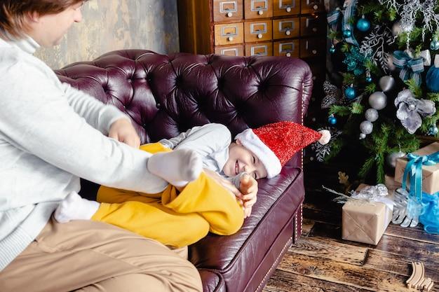 Gelukkig blanke vader kietelen veel plezier met opgewonden kleine peuter zoon in kerstmuts. ontspan samen, liefhebbende vader speelt met lachende kleine jongenskind, geniet van familieweekend thuis. vakantie concept.