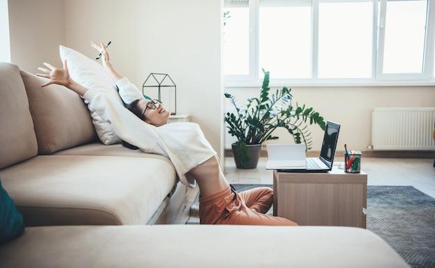 Gelukkig blanke vrouw die zich uitstrekt na het beëindigen van online lessen thuis op de vloer