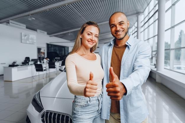 Gelukkig blanke vrouw en afro-amerikaanse man staan in de buurt van hun nieuwe auto