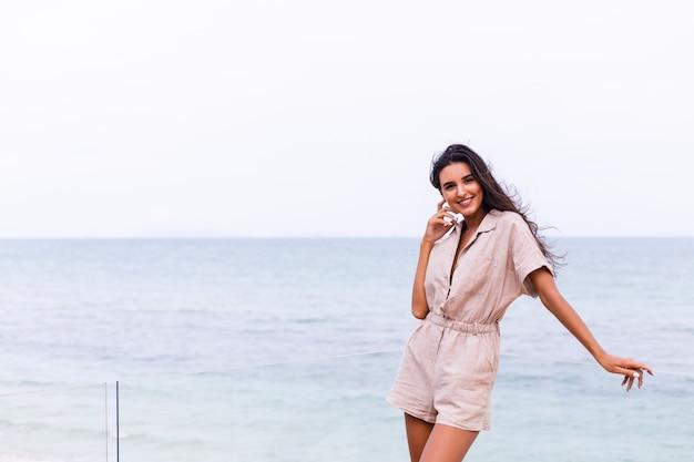 Gelukkig blanke vrouw in beige stijlvolle trebdy jumpsuit op winderige bewolkte dag op het strand