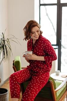 Gelukkig blanke vrouw in pyjama genieten van ochtend. binnen schot van innemende krullende vrouw met een kopje koffie.
