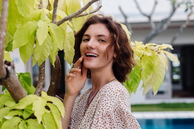 Gelukkig blanke vrouw kortom zomerjurk buiten villahotel door boom en blauw zwembad