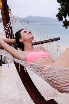 Gelukkig blanke vrouw ligt op hangmat in roze bikini aan het strand