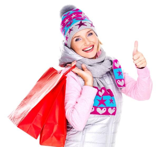 Gelukkig blanke vrouw met boodschappentassen toont duimen omhoog teken geïsoleerd op wit