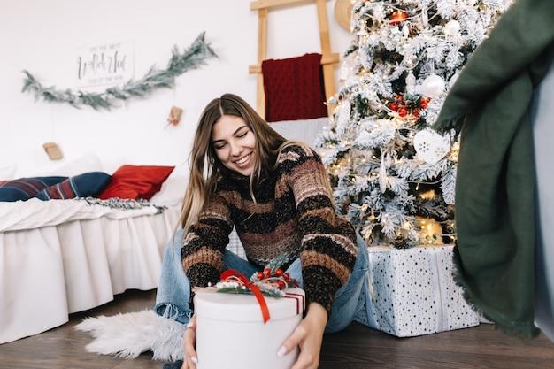 Gelukkig blanke vrouw met grote kerstcadeau zittend op de vloer thuis in de buurt van de kerstboom.