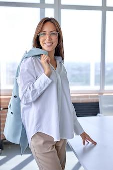 Gelukkig blanke vrouwelijke bedrijfsleider ceo baas executive poseren in modern kantoor