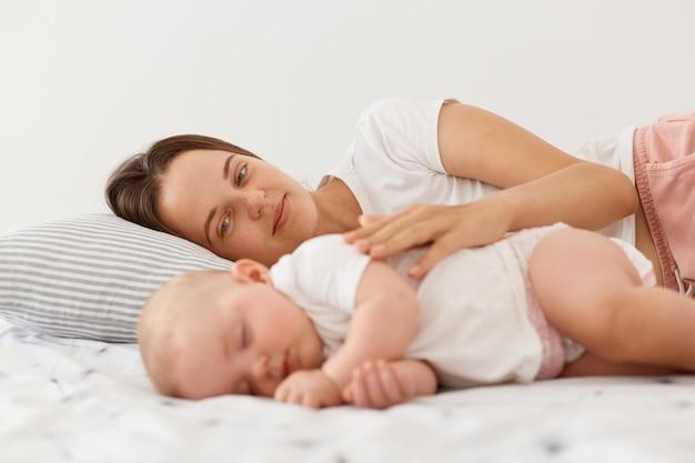 Gelukkig blij jonge donkerharige moeder en haar baby samen op bed liggen, mama knuffelen haar charmante dochter, mensen die witte kleding dragen, moederschap en jeugd.
