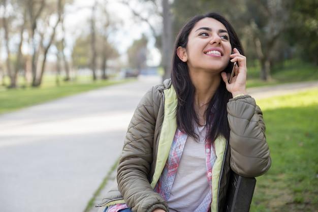 Gelukkig blij studentenmeisje dat op cel in park spreekt