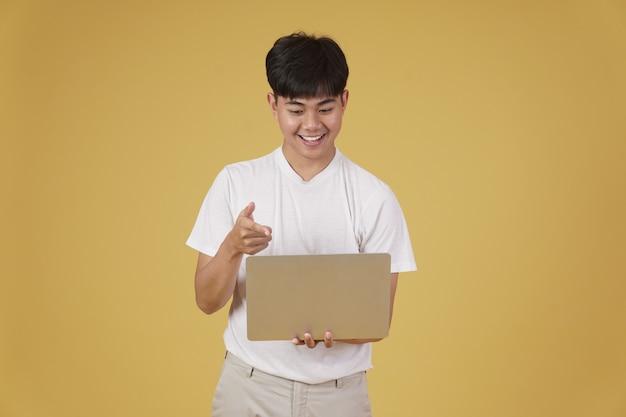 Gelukkig blij verheugend vrolijke jonge aziatische man gekleed terloops met wijzende vinger op laptop computerscherm geïsoleerd