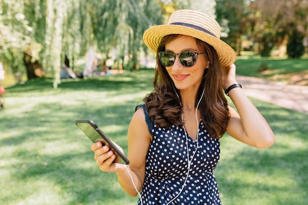 Gelukkig blij vrouw in hoed en zomerjurk luisteren muziek in het park
