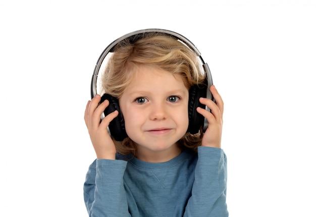 Gelukkig blond kind met koptelefoons een blauw t-shirt