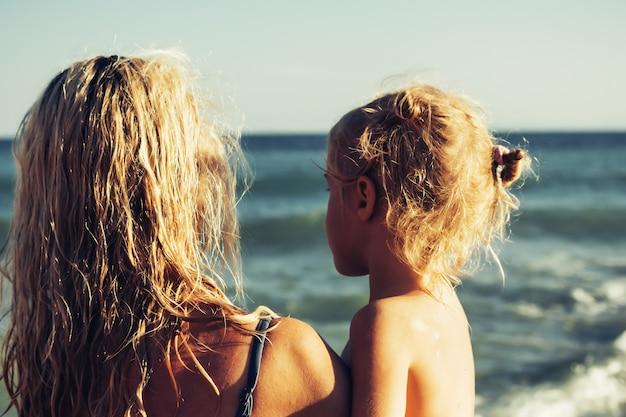 Gelukkig blond meisje in de armen van moeder op het strand. concept van een gelukkig gezin. vakantie concep