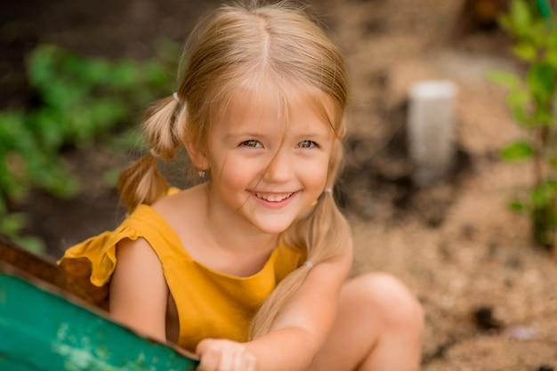 Gelukkig blond meisje in het land in een tuin kruiwagen vergadering glimlachen