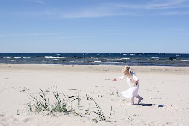 Gelukkig blond meisje in witte jurk loopt op het strand aan de kust van de oostzee.