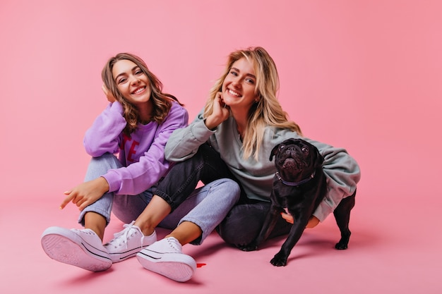 Gelukkig blond meisje omarmen bulldog puppy. betoverende vriendinnen ontspannen tijdens portretfotografie met huisdier.