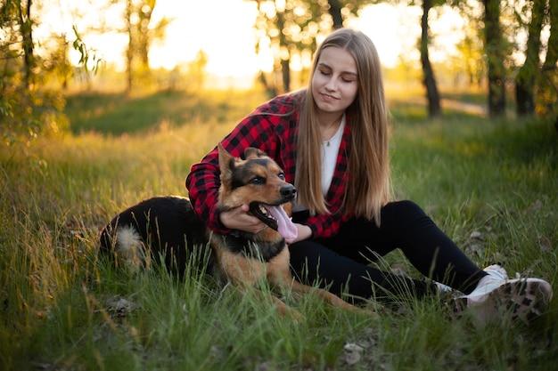 Gelukkig blond meisje wordt gespeeld met een hond.