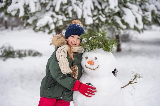 Gelukkig blond schattig kind meisje plaing met een sneeuwpop op een besneeuwde winterwandeling