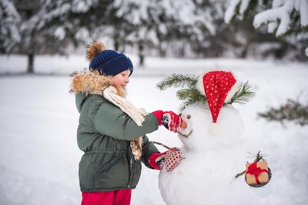 Gelukkig blond schattig kind meisje plaing met een sneeuwpop